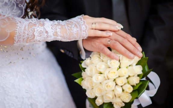 Bride and Groom with hands on bouquet