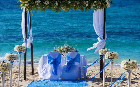 Decorated wedding table on beach under flowered arch
