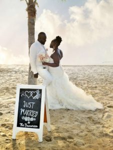 African American bride and groom on beach under palm tree